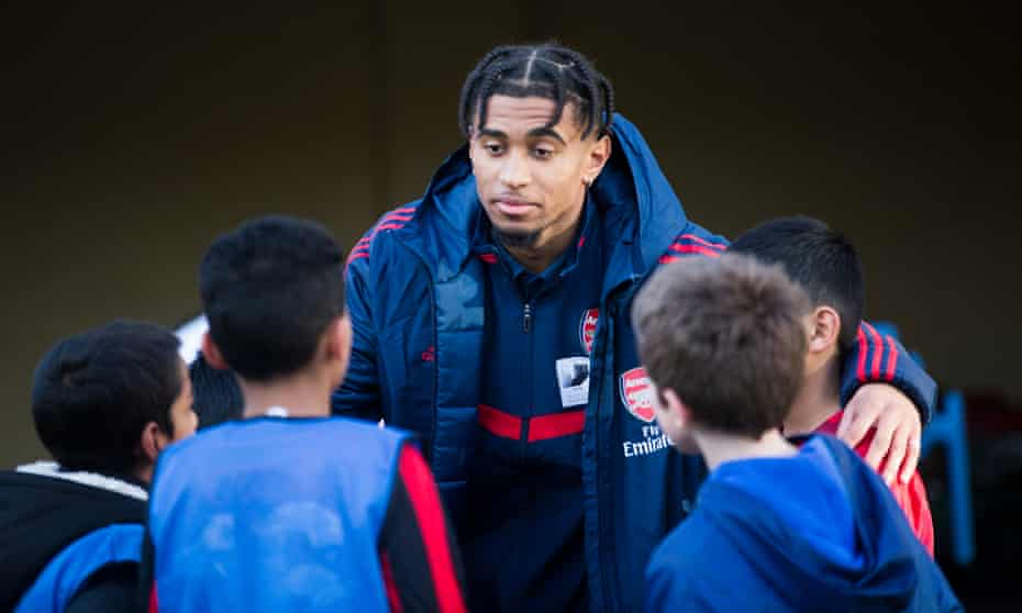 Reiss Nelson opens an artificial pitch at a London primary school. 'We had the gravel, the ones with little stones in it, so when you fall you get it in your knees and palms,' he says.