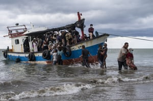 Aceh, Indonesia: local fishermen help Rohingya people as they arrive on Lancok beach. The fishermen discovered dozens of hungry, weak Rohingya Muslims on a wooden boat adrift off Indonesia's northernmost province