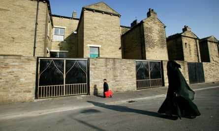 A Muslim mother and child walk down a terraced street in Bradford