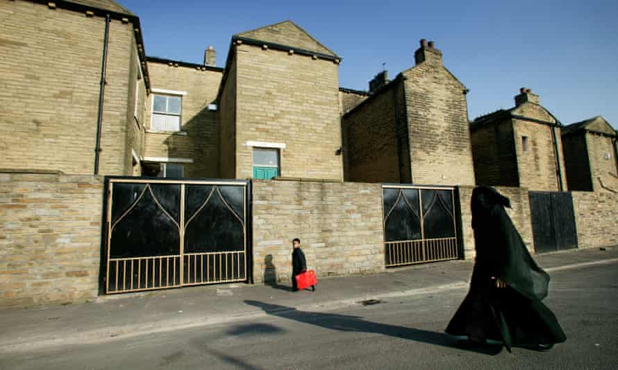 A mother and child walk by terraced houses in the Manningham area of Bradford.