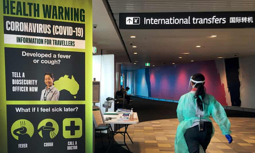 A staff member in protective medical clothing consults with arriving passengers at Brisbane international airport. Australia has strict new border measures to contain the spread of coronavirus. All overseas arrivals are required to self-isolate for 14 days.