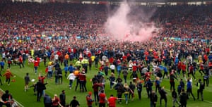 Middlesbrough fans invade the pitch after being promoted to the Premier League.