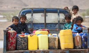 Children ride on the back of a truck loaded with water jerrycans at a camp for internally displaced people in the Dhanah area of the central province of Marib, Yemen, April 2016