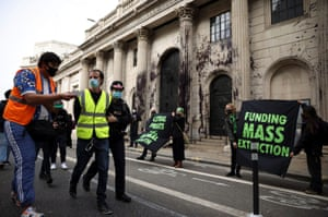 A police officer detaining an activist from Extinction Rebellion during a protest outside the Bank of England building