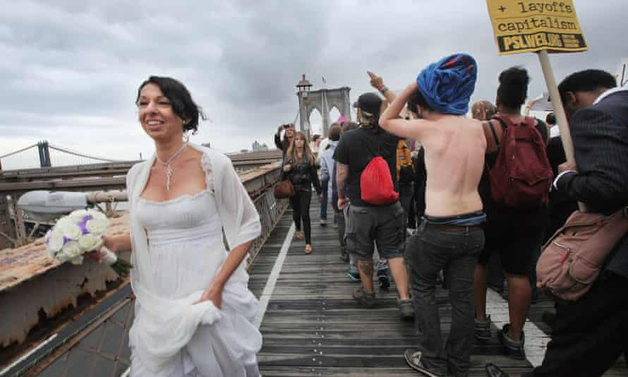 A bride walks past Occupy protesters as they cross the Brooklyn Bridge on 1 October 2011.