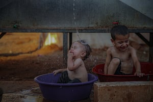Idlib, Syria: children try to cool off in washtubs during hot weather