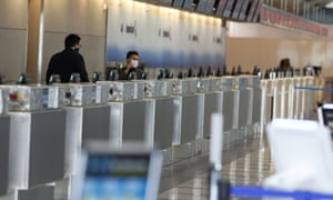 An agent adjusts his face mask while waiting for customers at a ticketing counter for American Airlines in the main terminal at Denver International Airport on Sunday 3 May, 2020.