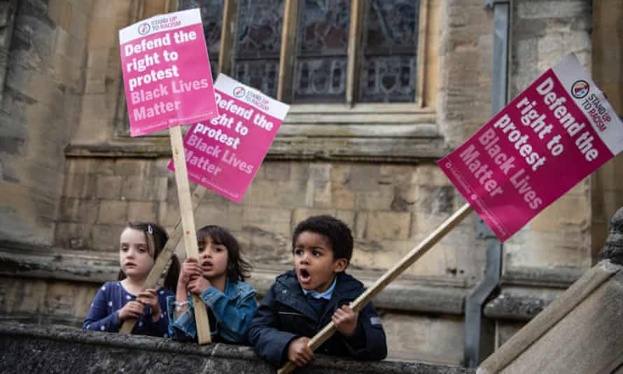 Young children hold placards during a march to Oriel Colleges statue of Cecil Rhodes at the University of Oxford.