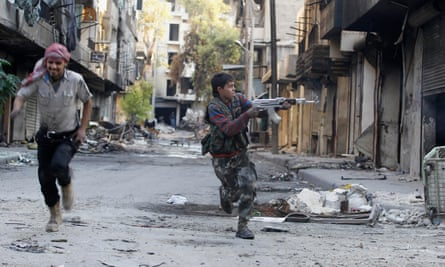 A 13-year-old fighter from the Free Syrian Army aims his weapon as he runs from snipers in Aleppo.