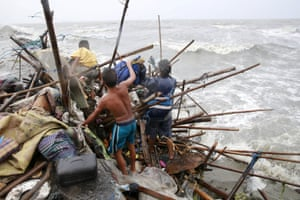 A Taroyo family living along the coast of Manila Bay searches for salvageable items after their house was damaged by typhoon Koppu in October 2015.