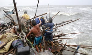 A family living along the coast of Manila Bay searches for salvageable items after their house was damaged by strong winds brought by typhoon.