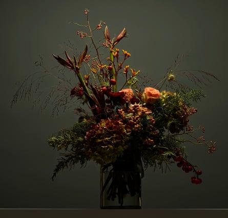 Table arrangement of red hydrangea, mimosa, blue thistles, crab apples, ilex, rosehip, amaryllis and kangaroo paw.