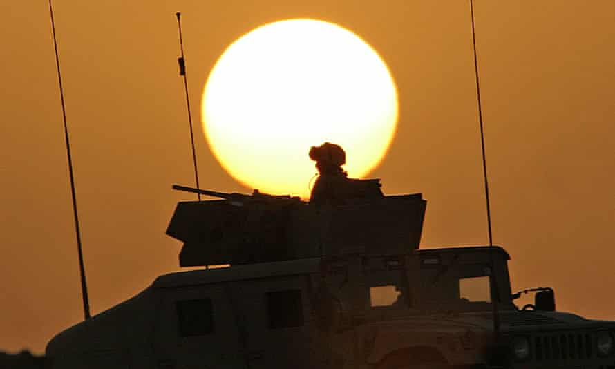 A US soldier sits atop a humvee at sunset in Iraq, 2006.