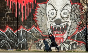 Vienna, Austria:A man holds his hat as he passes graffiti beside the Danube canal