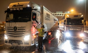 A police officer checks a lorry driver's information as lorries and thousands more vans wait to cross the Channel.