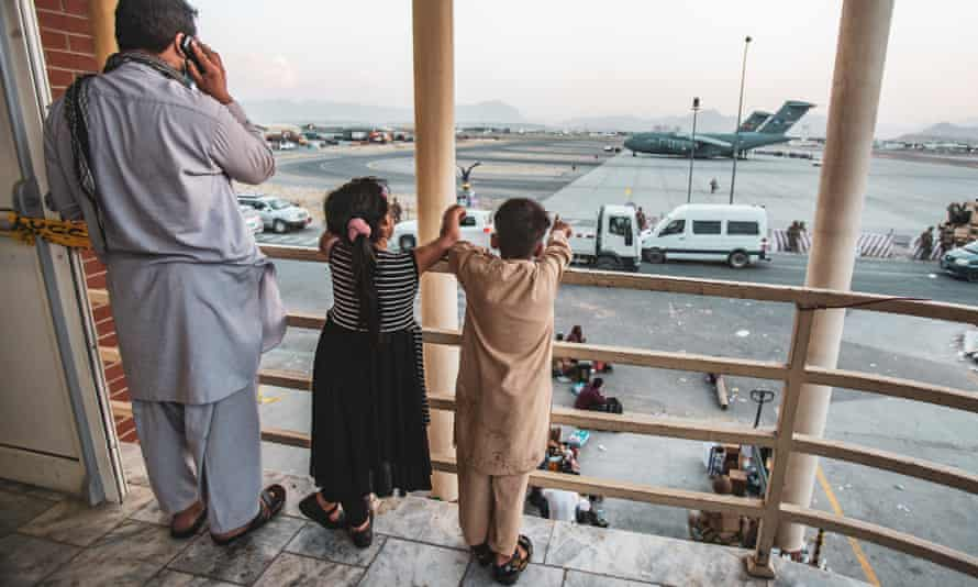 Two children point at an aircraft as they wait to be evacuated from Kabul airport.