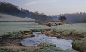 View of arched bridge over beck flowing through parkland at dawn, Hovingham Park, Hovingham, North Yorkshire, England, FebruaryE290P1 View of arched bridge over beck flowing through parkland at dawn, Hovingham Park, Hovingham, North Yorkshire, England, February