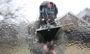A motorist scrapes ice from the windscreen of his car in freezing conditions in the US.
