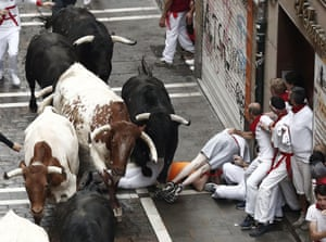 Runners try to avoid bulls as they run down a street
