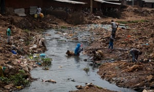 Children play by a river choked with plastic and human and animal waste that runs alongside the houses in the centre of Kibera. Areas like this increase the risk of infection, and reduce accessibility for Evalyne Nyangweso's paramedics.