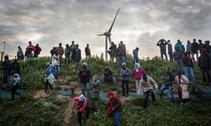 Migrants walk down a slope  leading to the Channel tunnel terminal.