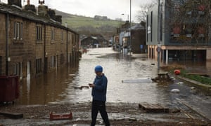 A man checks his phone as flood water covers the roads and car parks in Mytholmroyd, northern England, on February 9, 2020, after the River Calder burst its bank