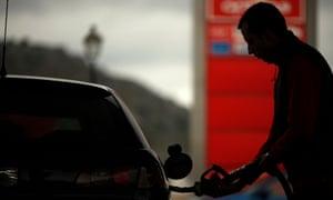 A worker pumps petrol into a customer's car at a petrol station in Cuevas del Becerro, near Malaga.