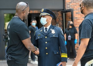 The Minneapolis police chief, Medaria Arradondo, center, shakes hands with a member of security as he leaves George Floyd's memorial in Minneapolis, Minnesota, on 04 June.