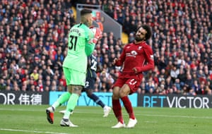 Ederson collects the ball as Salah runs in.