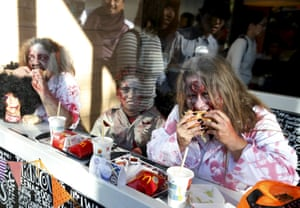 Participants in costume eat hamburgers inside a fast food restaurant after a Halloween parade in Kawasaki, Japan