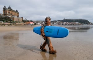 Will Hyde from Darlington wears a Chewbacca costume  as he carries a surfboard across the beach on the first day of the Scarborough Sci-fi weekend.