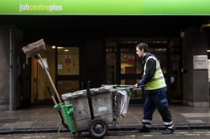 A street cleaner passes the Jobcentre Plus office in 2012 in Bath, England