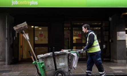 A street cleaner walks past a Jobcentre Plus office in Bath, England