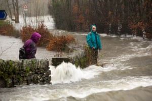 Walkers trying to cross raging flood waters on the Ambleside, Coniston road at Rothay bridge