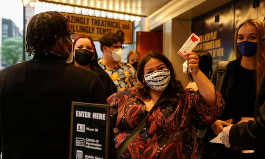 A guest waves her tickets while waiting in line at the opening night of previews for Pass Over, following the 17-month shutdown of Broadway
