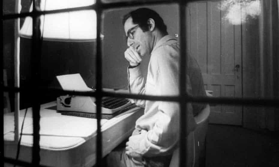 Roth sitting at typewriter seen through a window at Yaddo artist's retreat.