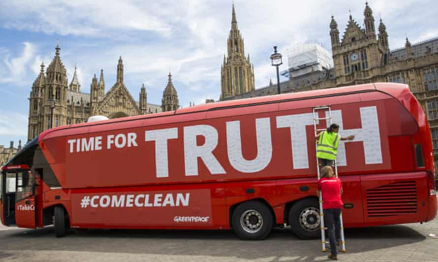 A Vote Leave battle bus is rebranded outside the Houses of Parliament by Greenpeace.