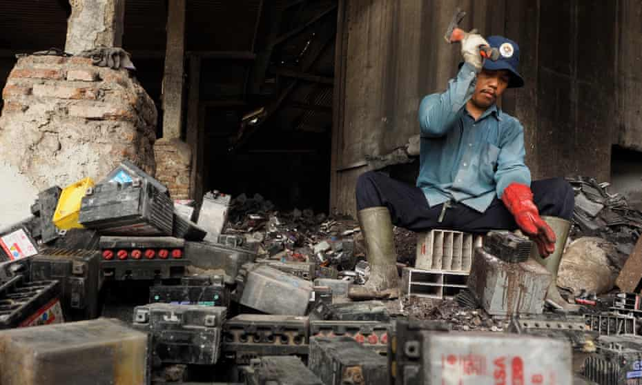 A man in Tegal, Indonesia, uses a hammer to break up used lead-acid batteries by hand.