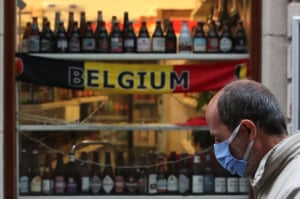 A man wearing a face mask walks past a shop selling beers, in central Brussels.
