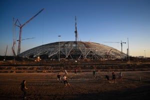 Men play football on the construction site of the Samara Arena.