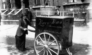 A baker wheeling her bread barrow through a London street, 1920.