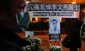 People wearing masks attend a vigil for Li Wenliang, an ophthalmologist who died of coronavirus at a hospital in Wuhan.