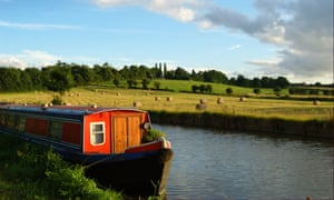 Canal Boat / Narrow Boat in late summer with Bales in Background