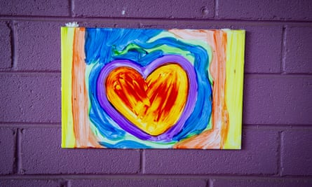 Painted heart with purple brick wall in the background