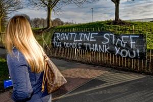 An NHS worker walks past a banner supporting NHS staff outside Salford Royal Hospital, Manchester
