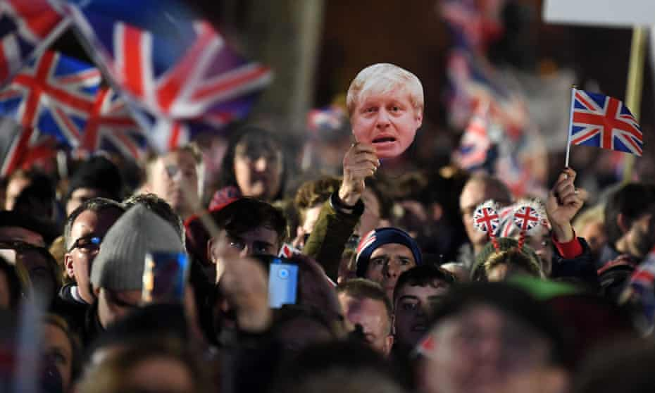 Brexit supporters wave flags and a mask of Boris Johnson in Parliament Square at 11pm on 31 January