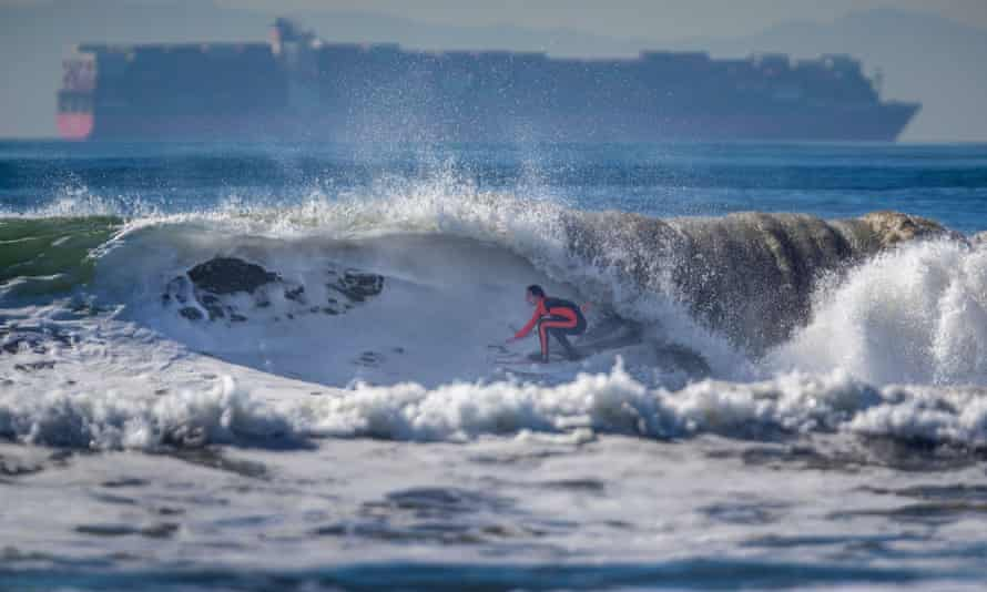 A surfer at Huntington beach on the Pacific coast of the US. Scientists expect about 1 metre of sea level rise by the end of the century.