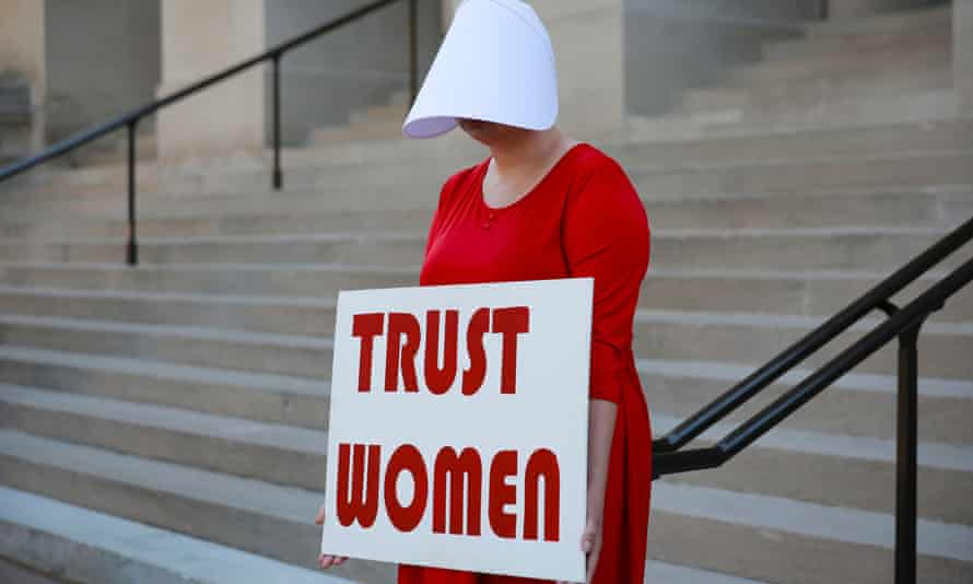 """Woman protests state's anti-abortion """"heartbeat"""" bill at Georgia State Capitol in Atlanta<br>A woman dressed as a Handmaid holds a sign reading 'Trust Women' in protest of Georgia's anti-abortion """"heartbeat"""" bill at the Georgia State Capitol in Atlanta, Georgia, U.S., May 7, 2019. REUTERS/Elijah Nouvelage"""