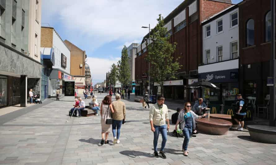 People walking through a wide pedestrianised shopping street in the sunshine.