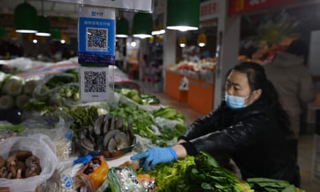 A vendor works behind QR payment codes at a market in Beijing.